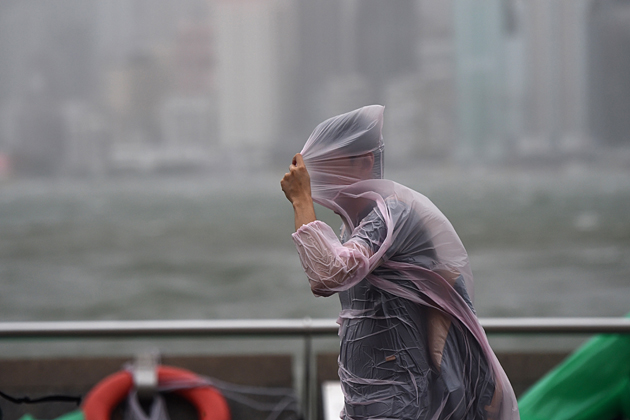 A man shields himself with his plastic poncho during heavy winds and rain brought on by Typhoon Hato in Hong Kong on August 23, 2017. Typhoon Hato smashed into Hong Kong on August 23 with hurricane force winds and heavy rains in the worst storm the city has seen for five years, shutting down the stock market and forcing the cancellation of hundreds of flights. / AFP PHOTO / Anthony WALLACE