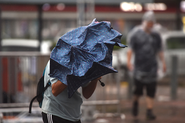 A man uses his umbrella as he walks on a street during heavy winds and rain brought on by Typhoon Hato in Hong Kong on August 23, 2017. Typhoon Hato smashed into Hong Kong on August 23 with hurricane force winds and heavy rains in the worst storm the city has seen for five years, shutting down the stock market and forcing the cancellation of hundreds of flights. / AFP PHOTO / Anthony WALLACE