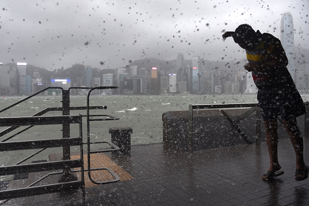 A man is splashed by the swell from Victoria Harbour during heavy winds and rain brought on by Typhoon Hato in Hong Kong on August 23, 2017. Typhoon Hato smashed into Hong Kong on August 23 with hurricane force winds and heavy rains in the worst storm the city has seen for five years, shutting down the stock market and forcing the cancellation of hundreds of flights. / AFP PHOTO / Anthony WALLACE