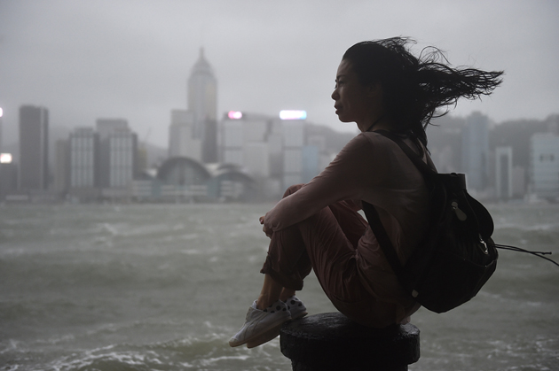 A woman looks out to Victoria Harbour during heavy winds and rain brought on by Typhoon Hato in Hong Kong on August 23, 2017. Typhoon Hato smashed into Hong Kong on August 23 with hurricane force winds and heavy rains in the worst storm the city has seen for five years, shutting down the stock market and forcing the cancellation of hundreds of flights. / AFP PHOTO / Anthony WALLACE