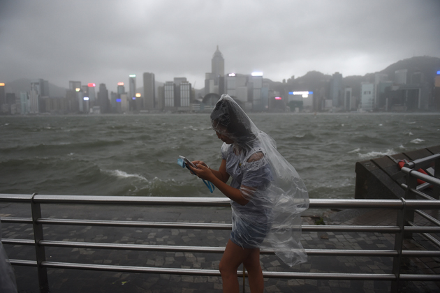 A woman uses her phone while wearing a plastic poncho along Victoria Harbour during heavy winds and rain brought on by Typhoon Hato in Hong Kong on August 23, 2017. Typhoon Hato smashed into Hong Kong on August 23 with hurricane force winds and heavy rains in the worst storm the city has seen for five years, shutting down the stock market and forcing the cancellation of hundreds of flights. / AFP PHOTO / Anthony WALLACE