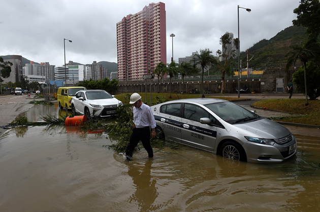 A man wades through floodwaters away from his car after heavy rains brought on by Typhoon Hato in Hong Kong on August 23, 2017. Typhoon Hato smashed into Hong Kong on August 23 with hurricane force winds and heavy rains in the worst storm the city has seen for five years, shutting down the stock market and forcing the cancellation of hundreds of flights. / AFP PHOTO / Anthony WALLACE