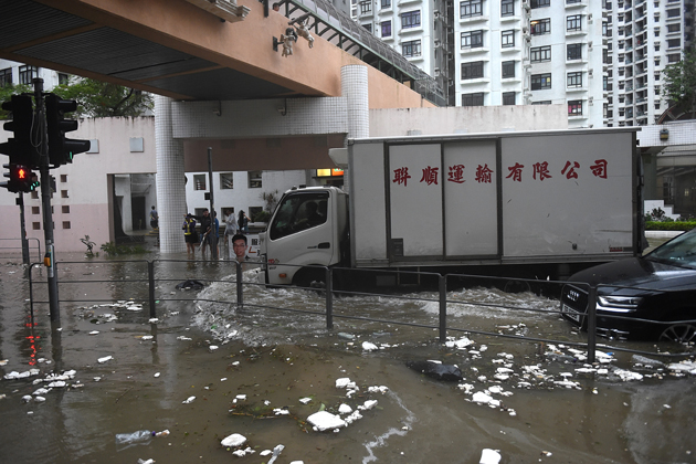 Commuters drive along a flooded road after heavy rains brought on by Typhoon Hato in Hong Kong on August 23, 2017. Typhoon Hato smashed into Hong Kong on August 23 with hurricane force winds and heavy rains in the worst storm the city has seen for five years, shutting down the stock market and forcing the cancellation of hundreds of flights. / AFP PHOTO / Anthony WALLACE