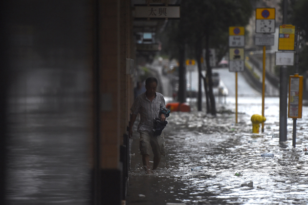 A man wades through floodwaters on a street after heavy rains brought on by Typhoon Hato in Hong Kong on August 23, 2017. Typhoon Hato smashed into Hong Kong on August 23 with hurricane force winds and heavy rains in the worst storm the city has seen for five years, shutting down the stock market and forcing the cancellation of hundreds of flights. / AFP PHOTO / Anthony WALLACE