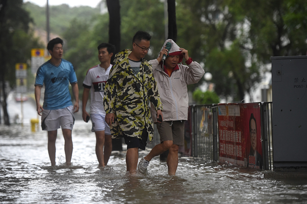 Pedestrians walk through floodwaters along a street after heavy rains brought on by Typhoon Hato in Hong Kong on August 23, 2017. Typhoon Hato smashed into Hong Kong on August 23 with hurricane force winds and heavy rains in the worst storm the city has seen for five years, shutting down the stock market and forcing the cancellation of hundreds of flights. / AFP PHOTO / Anthony WALLACE