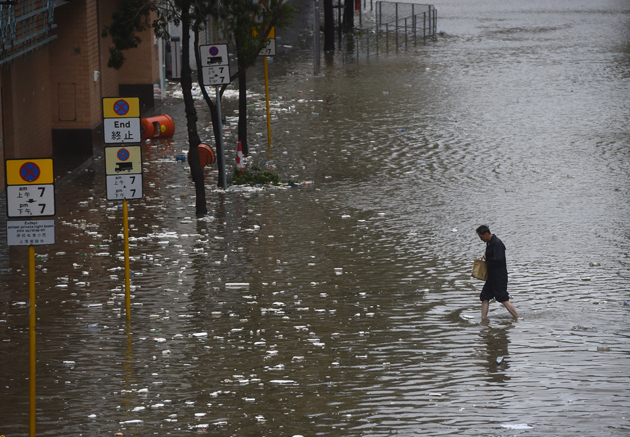 A man walks across a flooded street in the Heng Fa Chuen area as Typhoon Hato hits Hong Kong on August 23, 2017. Heavy rains and driving winds lashed Hong Kong on August 23 shutting schools and the stock market and bringing chaos to the city's international airport where hundreds of flights were cancelled. / AFP PHOTO / Anthony WALLACE