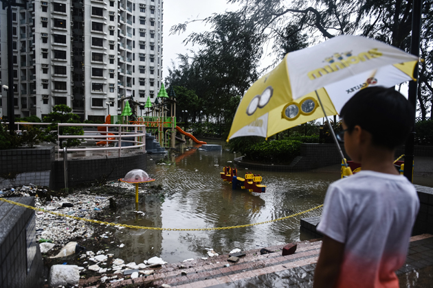 A young child looks at a flooded playground and marine debris after heavy winds and rains brought on by Typhoon Hato in Hong Kong on August 23, 2017. Typhoon Hato left three dead in the gambling hub of Macau on August 23 as it brought chaos and destruction to the enclave after sweeping through neighbouring Hong Kong, where one man also died. / AFP PHOTO / Anthony WALLACE