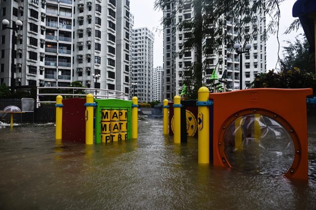 A flooded playground is seen in front of residential blocks after heavy rains brought on by Typhoon Hato in Hong Kong on August 23, 2017. Typhoon Hato left three dead in the gambling hub of Macau on August 23 as it brought chaos and destruction to the enclave after sweeping through neighbouring Hong Kong, where one man also died. / AFP PHOTO / Anthony WALLACE